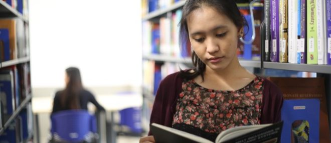 Student Reading A Book In The Miu Library